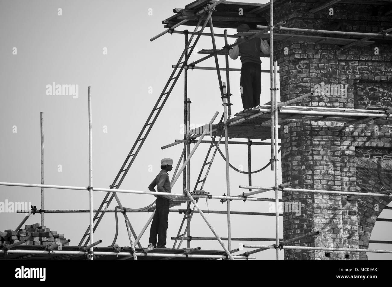 'Brick by brick'.  Monochrome image of construction site workers on scaffolding. Bamboo poles, a ladder and basic lifting equipment are the only tools - Stock Image