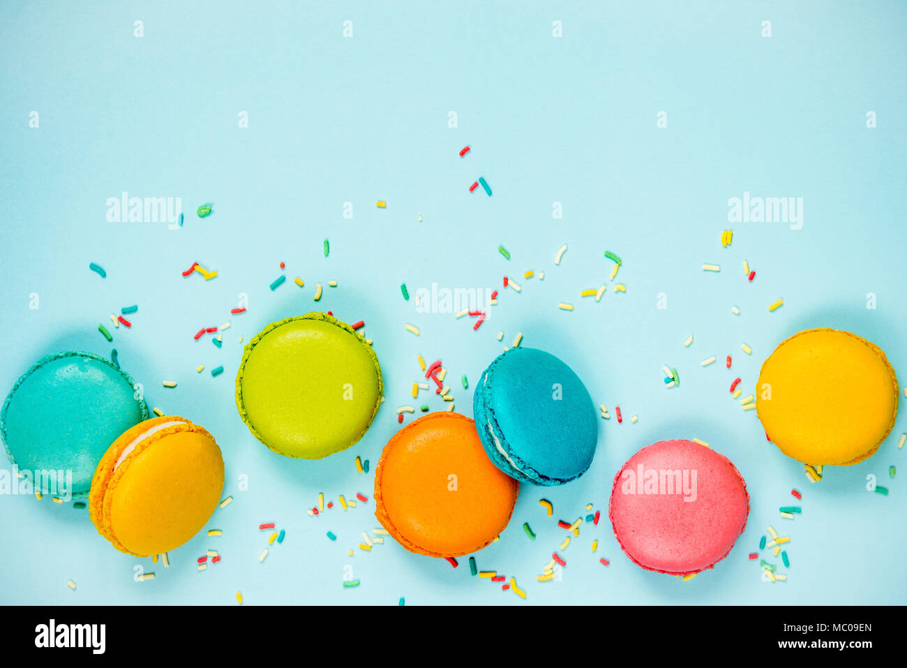 Top view of colorful macaroons and sugar sprinkles arranged over blue background. - Stock Image