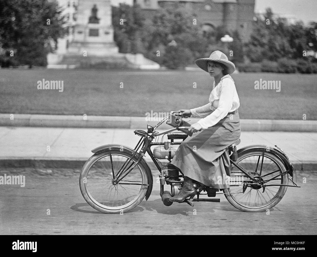 Girl on motorized bicycle, circa 1917 - Stock Image