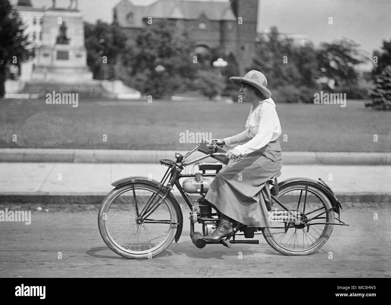 A young girl on a motorized bicycle, circa 1918 - Stock Image