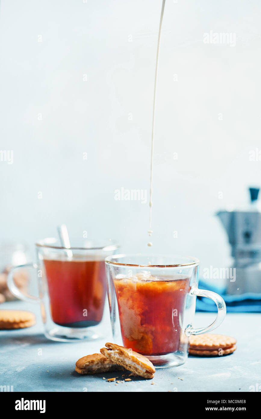 Morning coffee with cookies. Double wall glass cups with a Moka pot on a light concrete background. Pouring milk in coffee action food photography - Stock Image