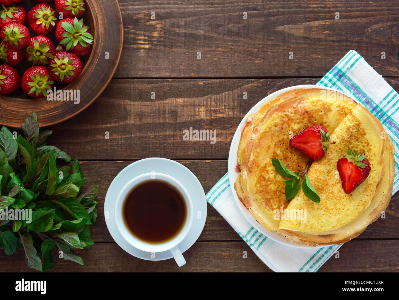 Pile of golden pancakes with strawberries and strawberry jam, decorative sprig of mint. The top view - Stock Image