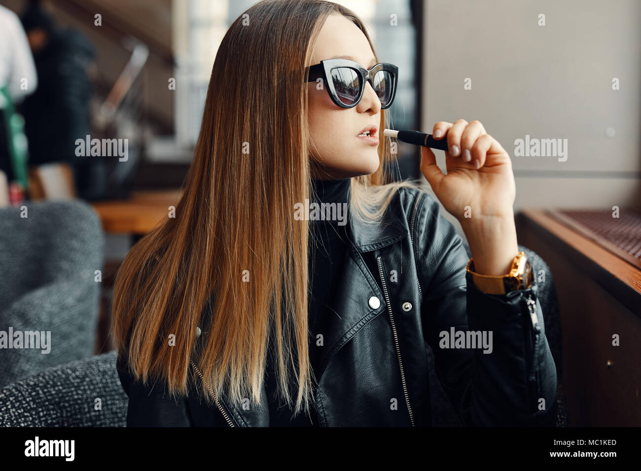 Girl sit in caffee place and smoke electronic cigarette wear glasses - Stock Image