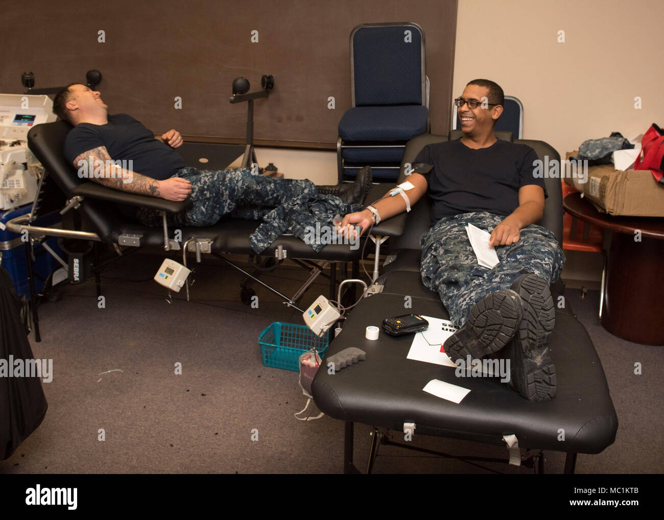 180124-N-LI612-027 KINGS BAY (Jan. 24, 2018) Chief Machinist's Mate (Nuclear) Jace Haster, left, shares a laugh with Electricians Mate 3rd Class Ryan Shaw during a blood drive onboard Naval Submarine Base Kings Bay (NSBKB). NSBKB is the east coast home to the Ohio-class submarine. (U.S. Navy photo by Mass Communication Specialist 2nd Class Eli K. Buguey/Released.) - Stock Image