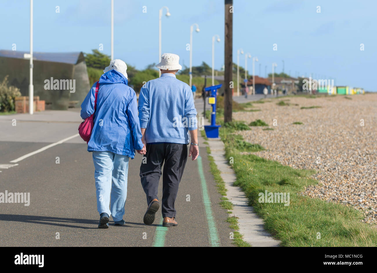 Senior couple walking away holding hands along the seafront promenade, on a sunny day in Littlehampton, West Sussex, England, UK. seafront stroll. Stock Photo