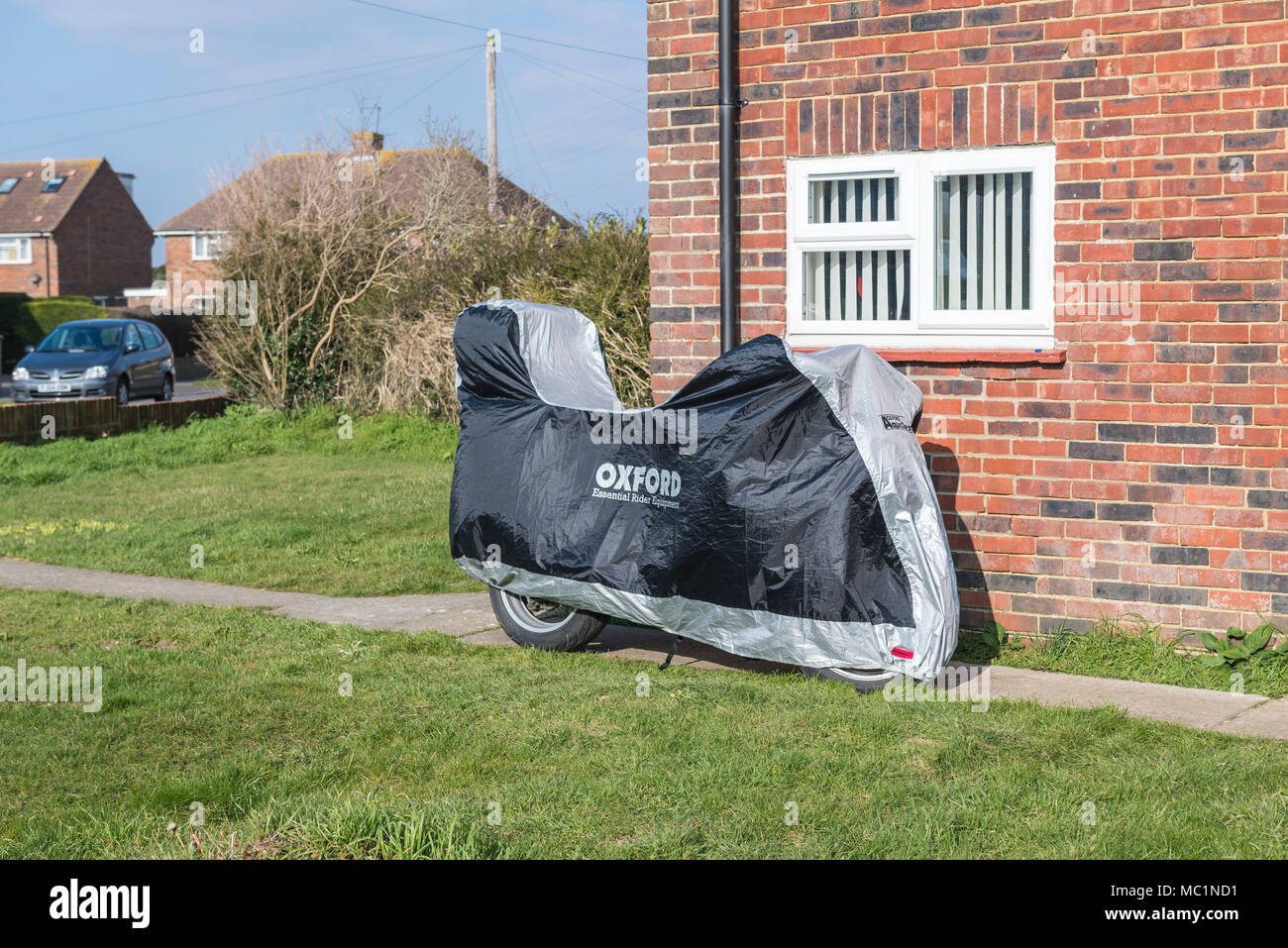 A motorcycle parked outside a house with a protective cover over it. Covered motorbike. - Stock Image
