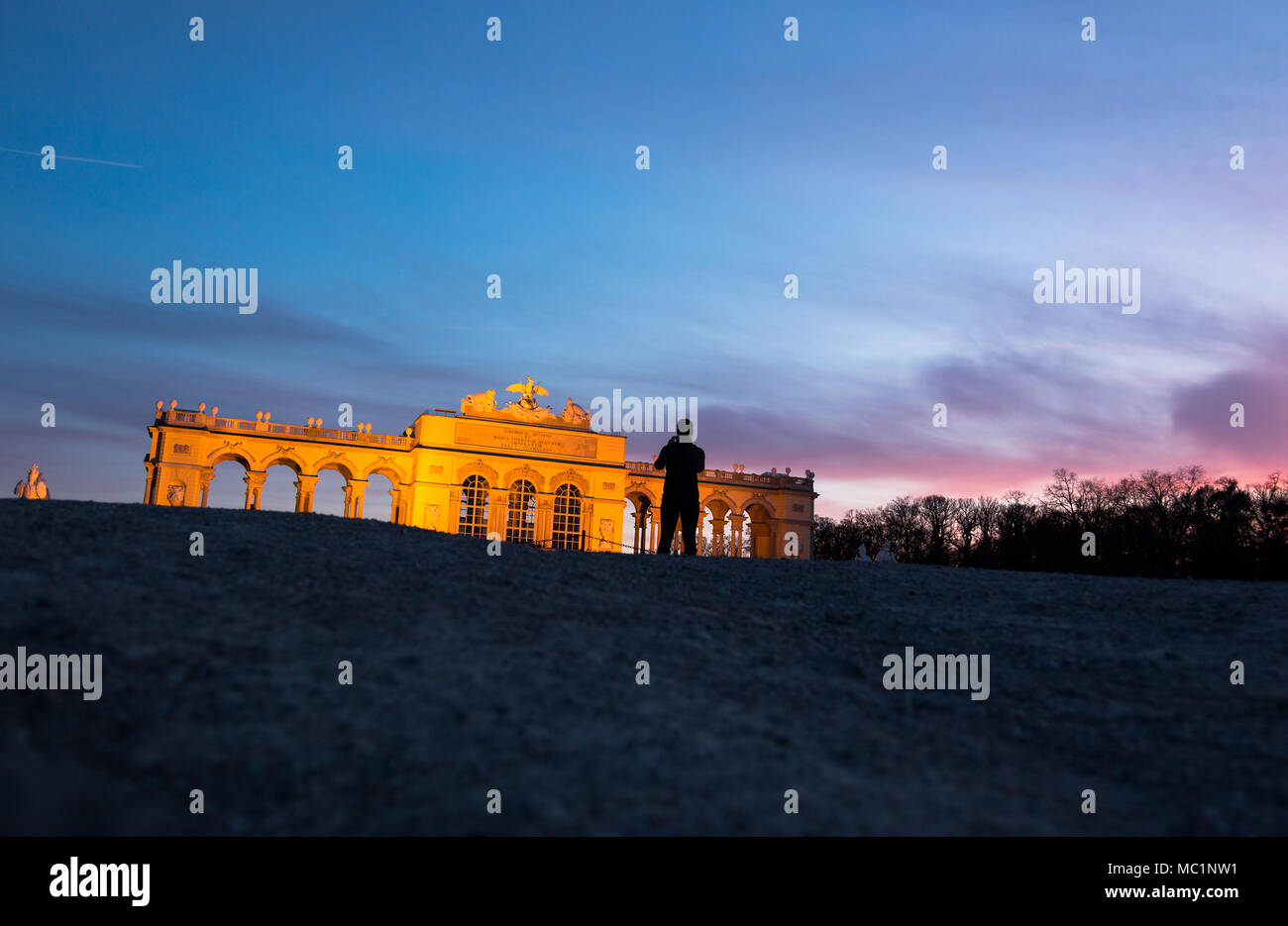 Gloriette in Schönbrunner Schloss Park at late evening in golden hour light. Low, wide angle perspective, shoot from ground level. Tourist making a ph - Stock Image