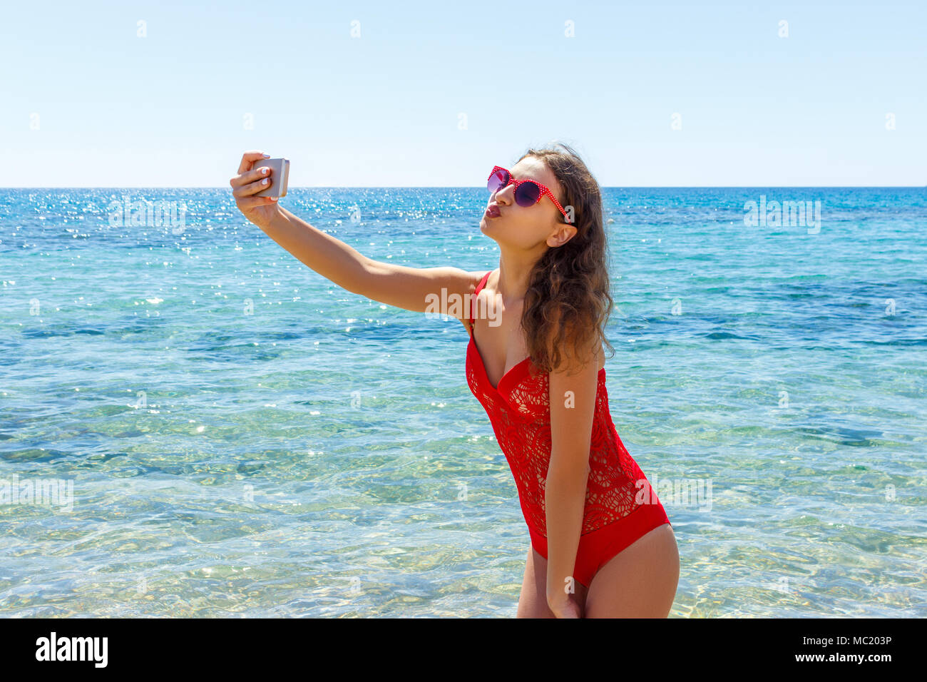 Summer beach vacation girl taking fun mobile selfie photo with smartphone. Girl wearing red sunglasses posing for selfie. - Stock Image