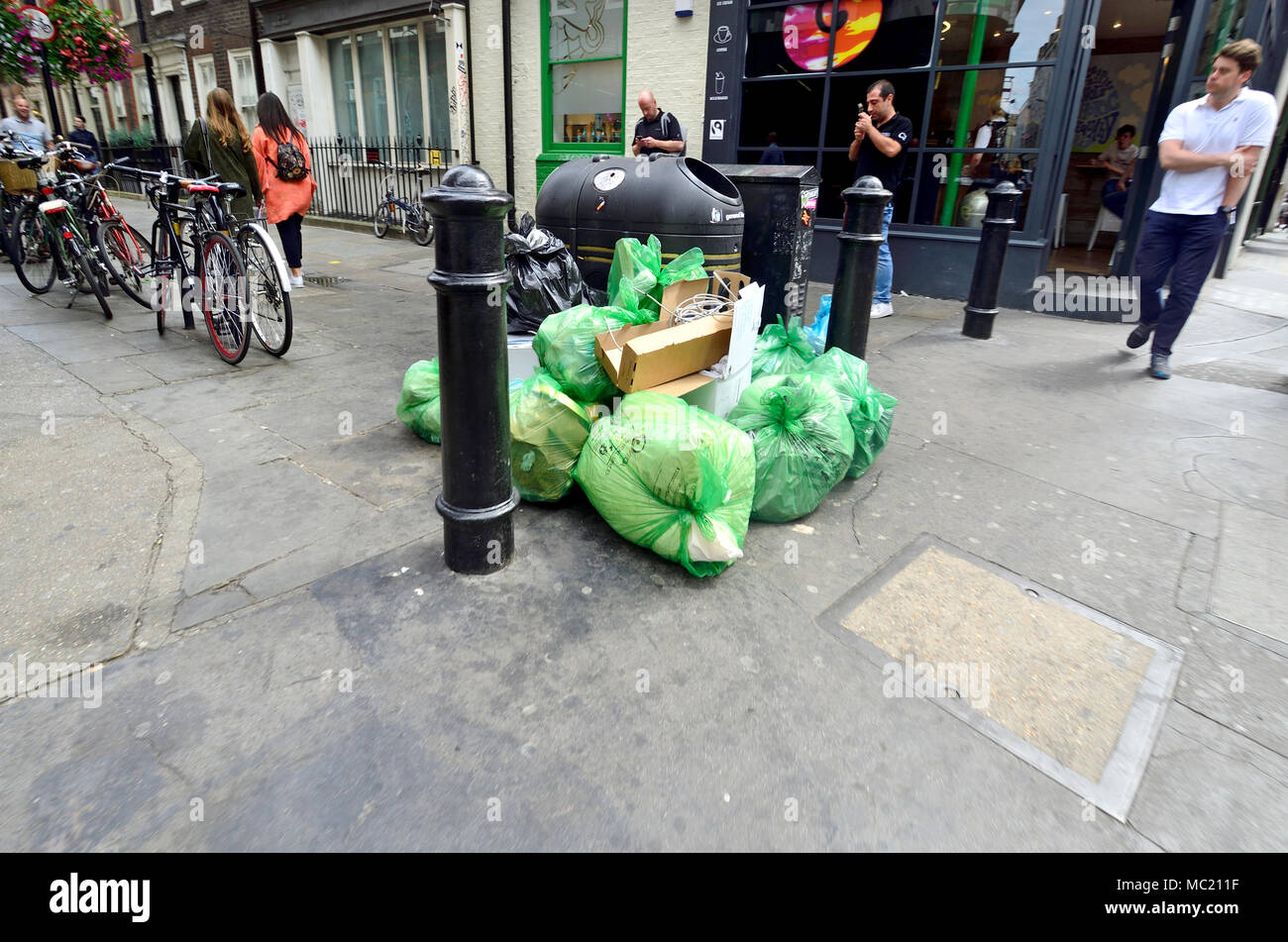 London, England, UK. Rubbish bags dumped around a bin in the street - Stock Image