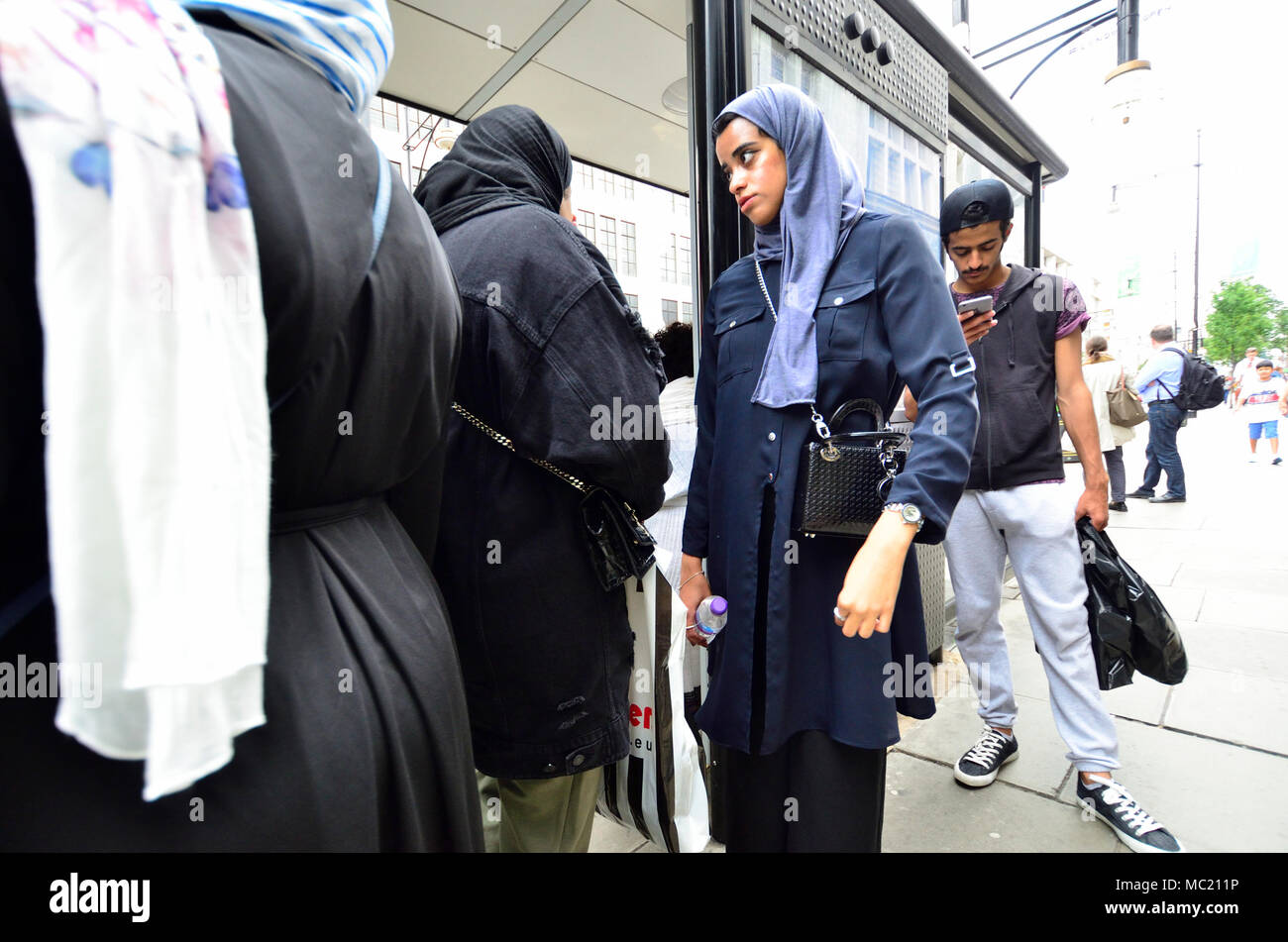 London, England, UK. Muslim women wearing headscarves at a bus stop - Stock Image