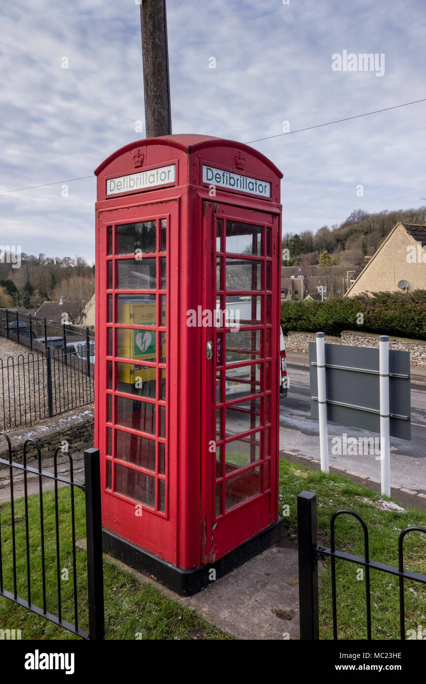 Disused red telephone box now converted to Defibrillator station for emergency, Avening, Gloucestershire, UK - Stock Image