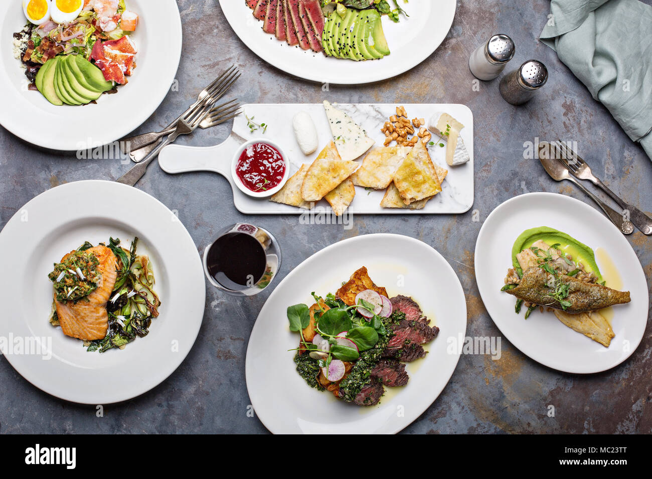 Big dinner table overhead view with steak and fish - Stock Image