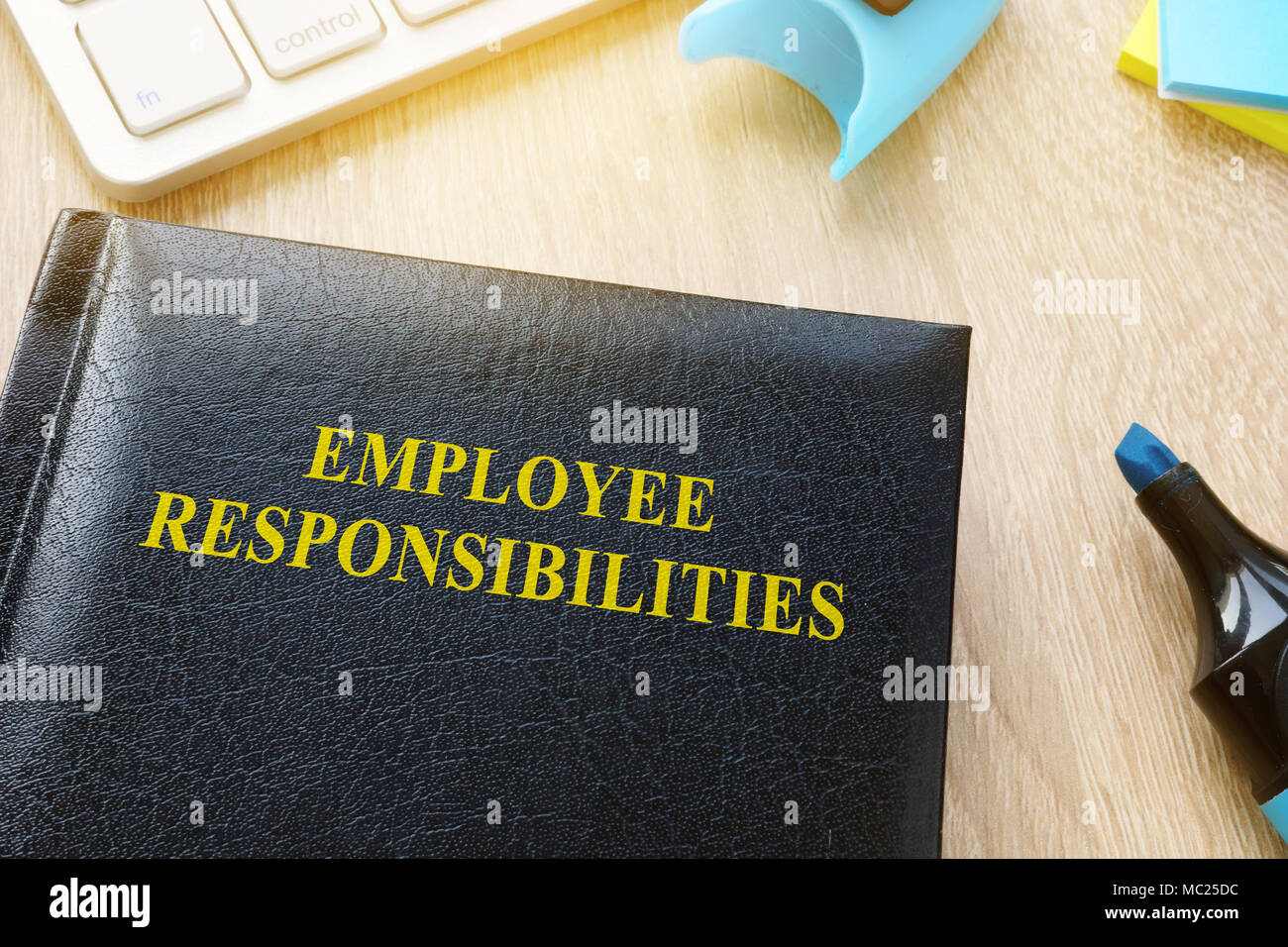 Book about Employee responsibilities on an office table. - Stock Image
