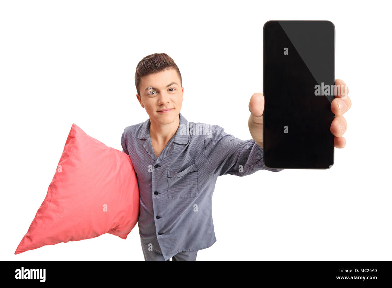 Teenage boy in pajamas holding a pillow and a phone isolated on white background - Stock Image
