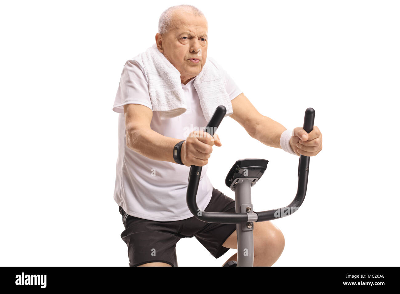 Tired mature man working out on an exercise bike isolated on white background - Stock Image