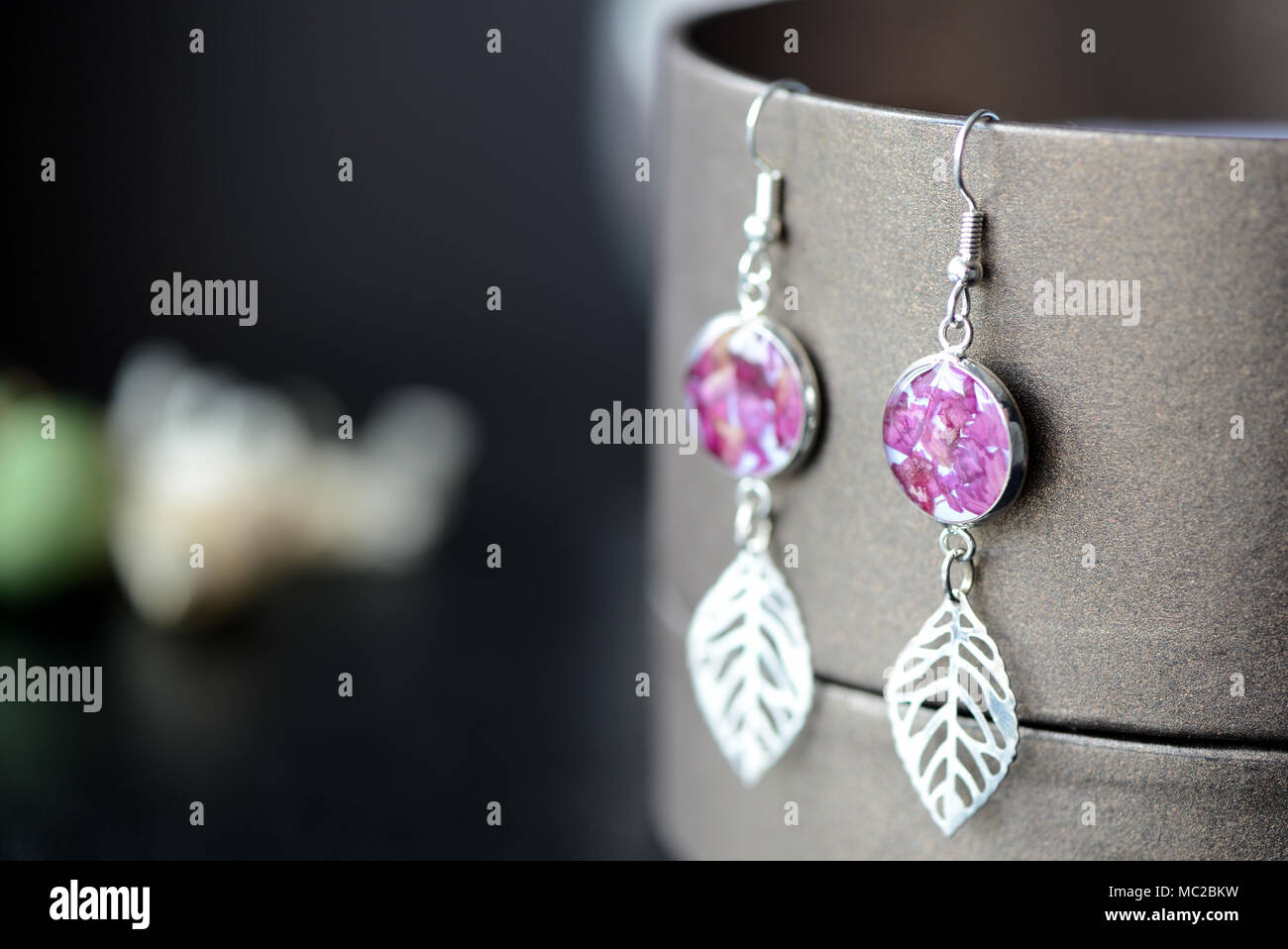 a222454d1 Dangle earrings made of epoxy resin and dried rose petals close up - Stock  Image