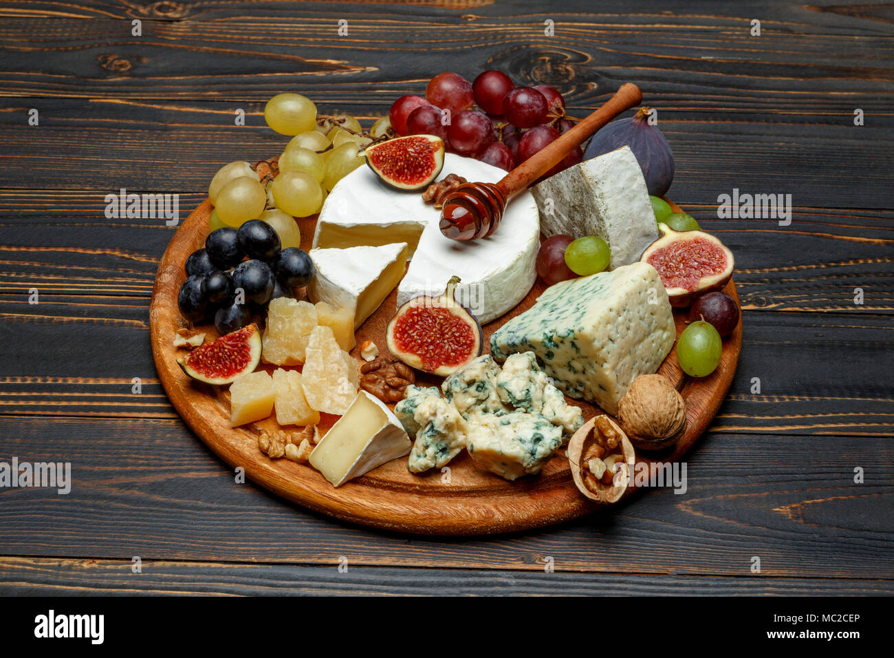 Brie cheese on a wooden Board with fresh figs and grapes - Stock Image