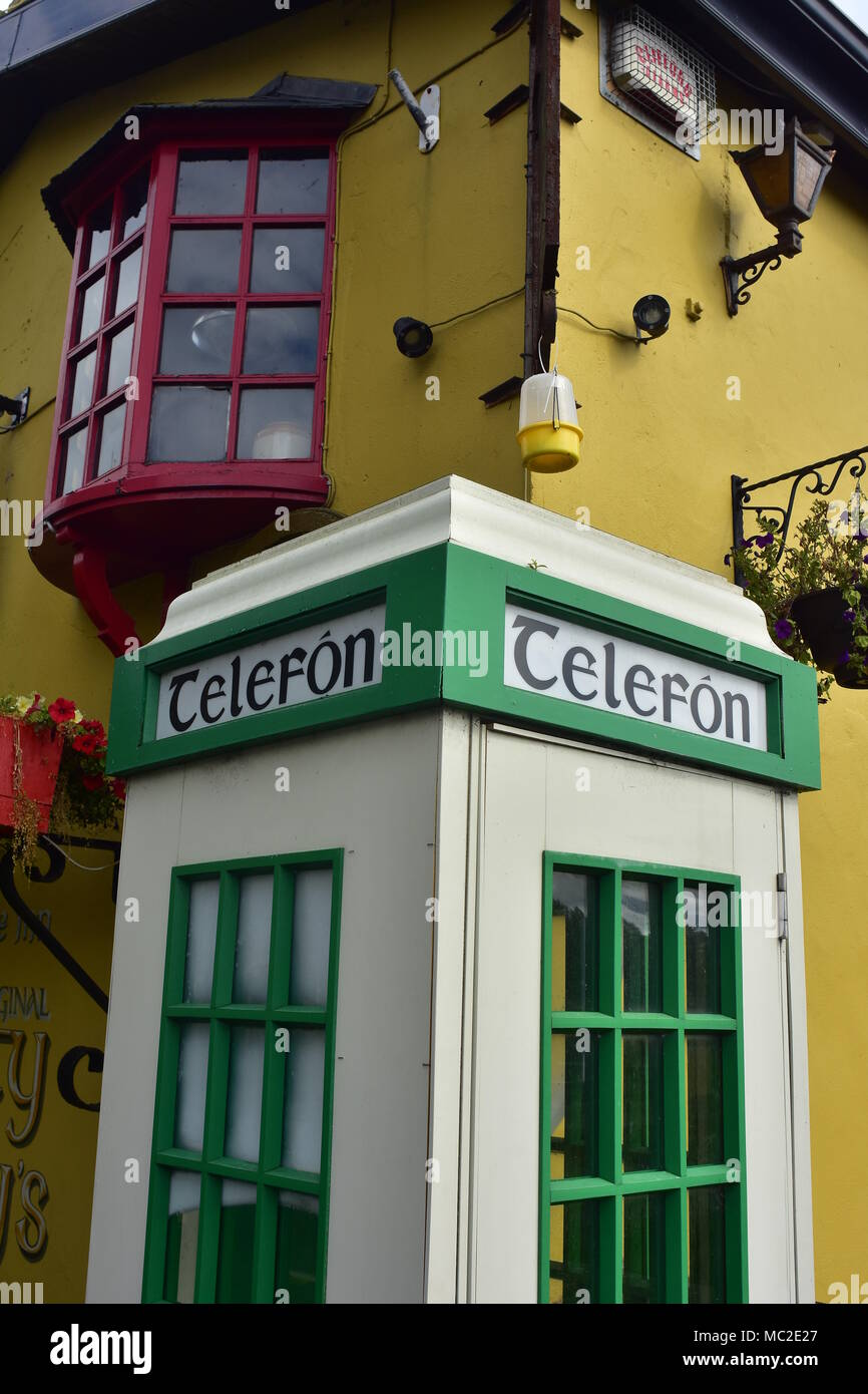 White and green vintage pay phone booth at bright yellow Irish in with hotel in Bunratty. - Stock Image