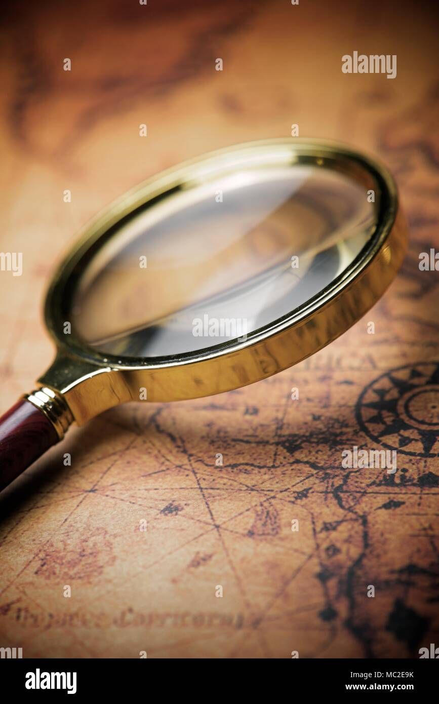 Magnifying glass and old navigation map. - Stock Image