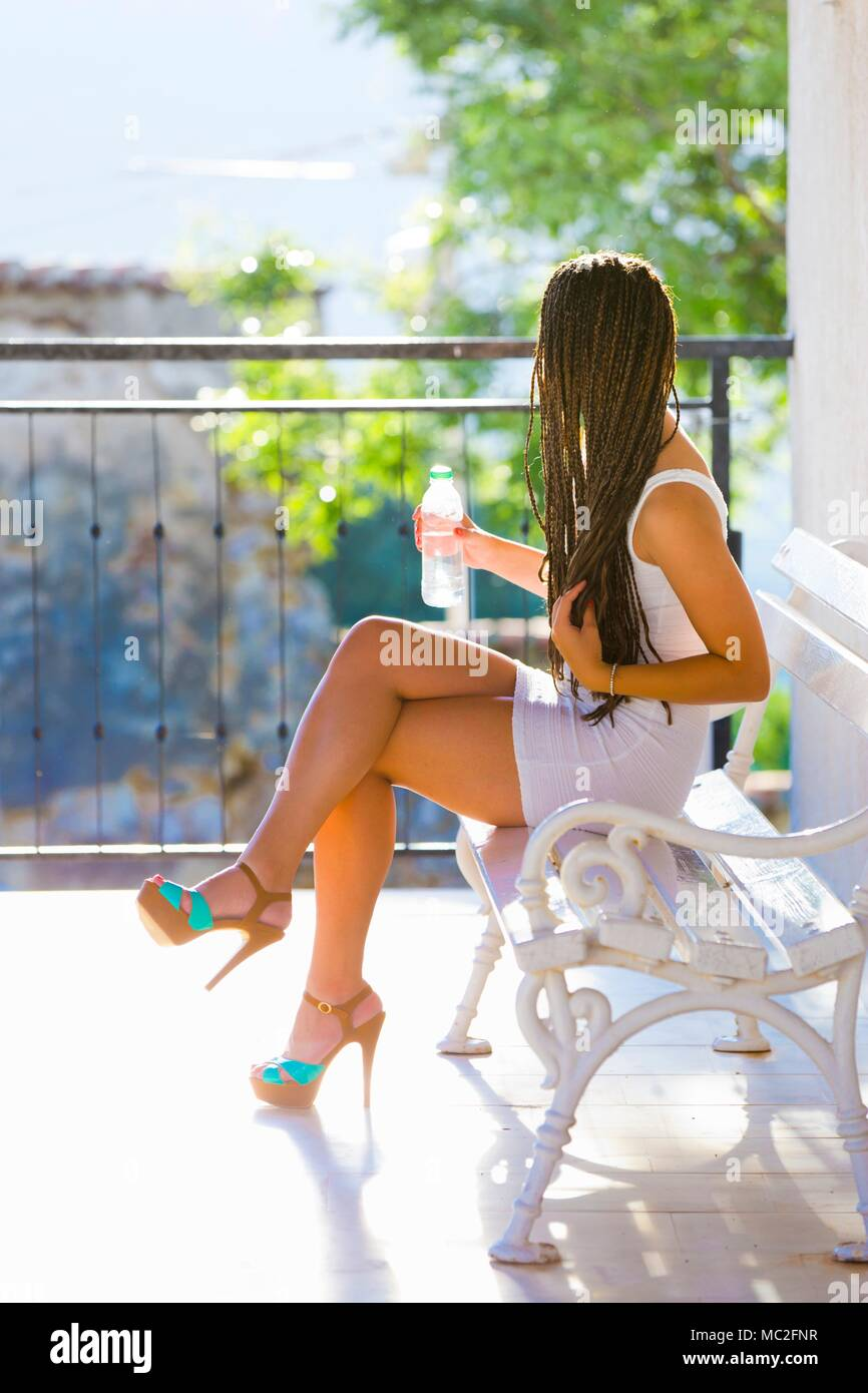 Teen girl legs heels sundress  looking aside spike spiked - Stock Image