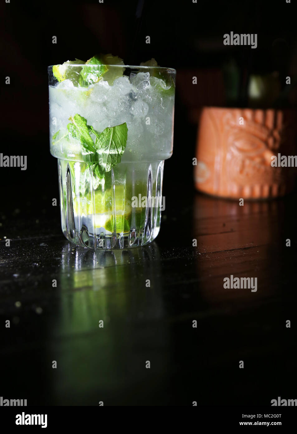 cocktail drinks with lime juice and grated ice on black background - Stock Image