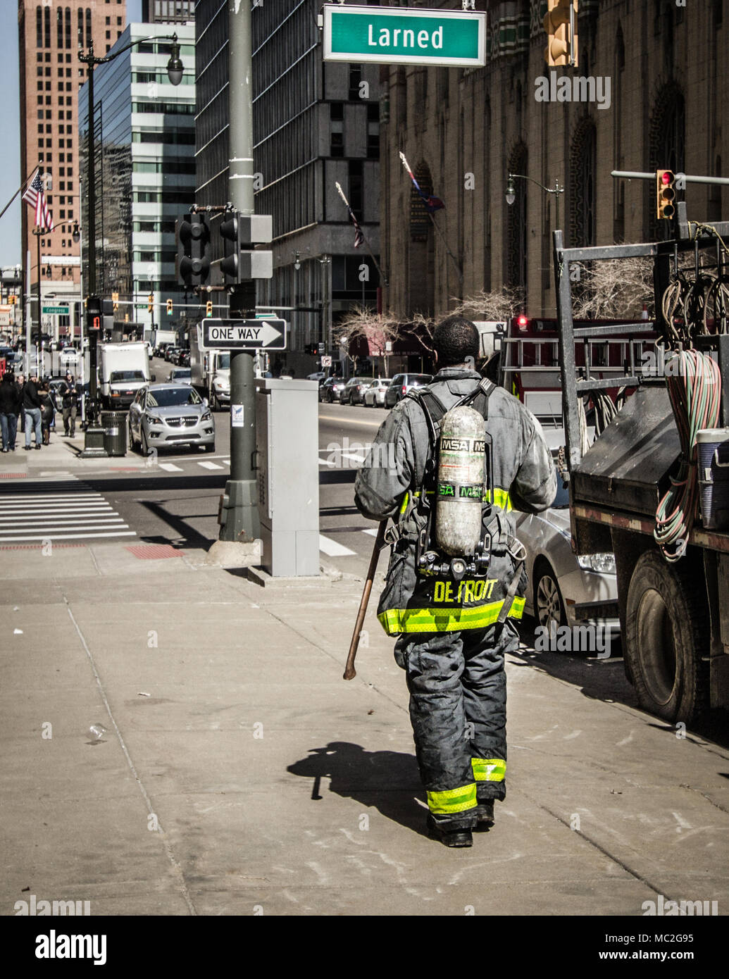 Detroit, Michigan, USA - March 22, 2018: Detroit firefighter walking down a city sidewalk after responding to a call - Stock Image