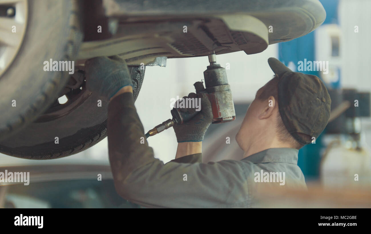 Mechanic unscrews detail of car in hood - automobile service repairing, close up - Stock Image