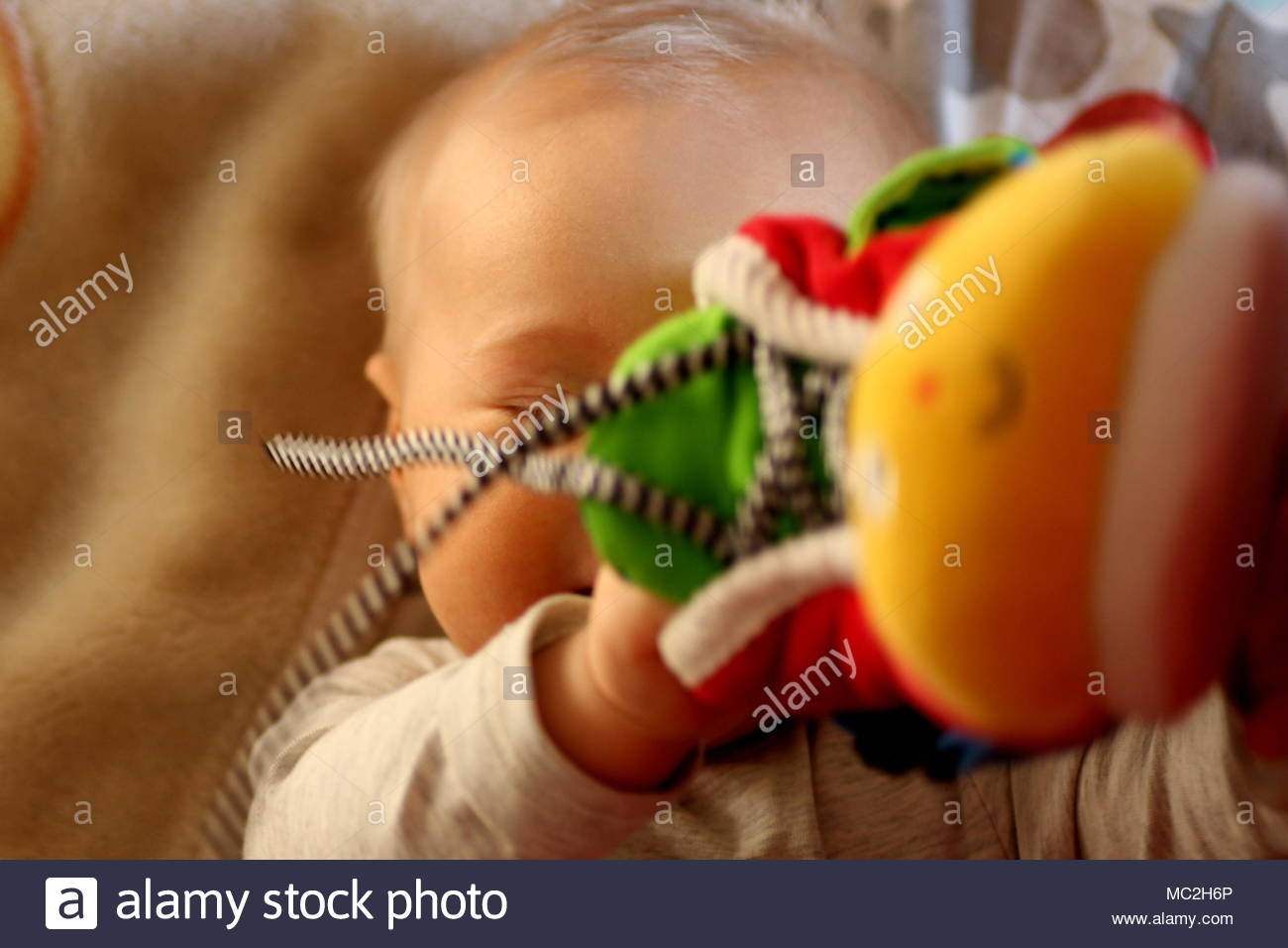A baby playing with toy - Stock Image