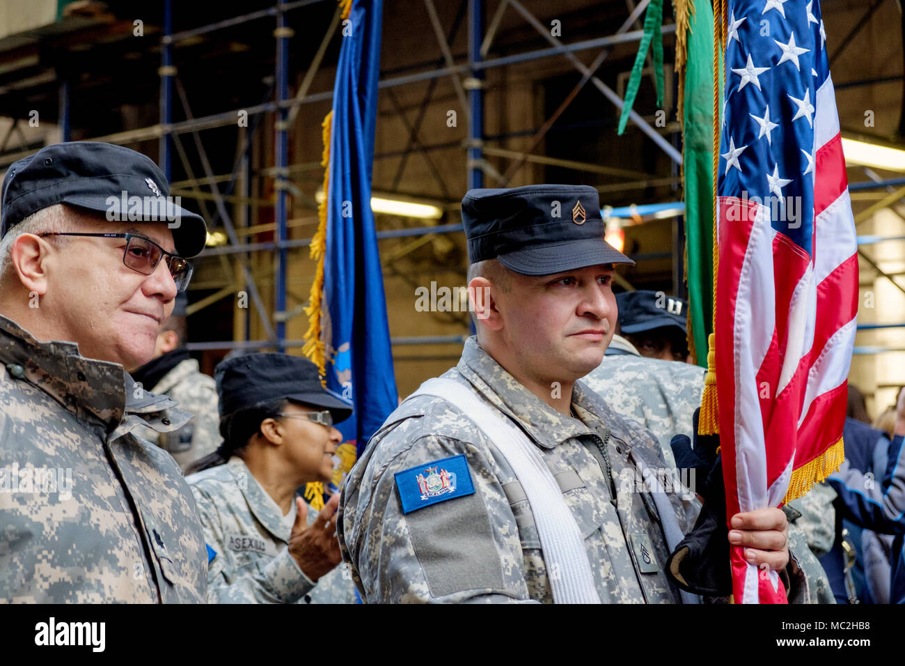 Two men march with 88th Brigade, New York Guard  in St. Patrick's Day Parade, New York, 2018. One holds American flag. Uniforms, blue caps. Close up. - Stock Image