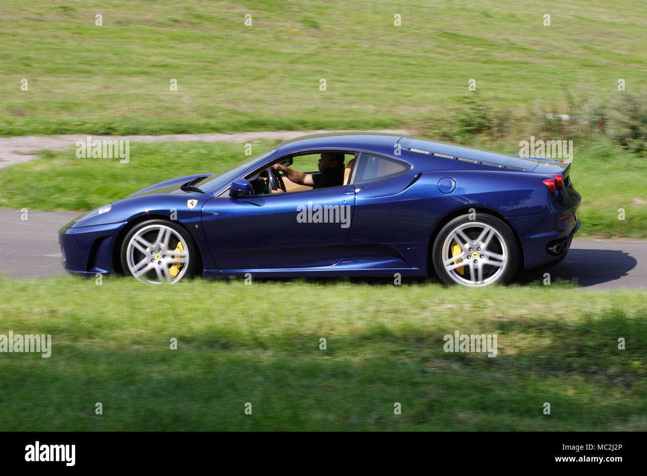Blue Ferrari 360 entry level used Ferrari sportscar, driving fast and photographed in profile (side view). - Stock Image