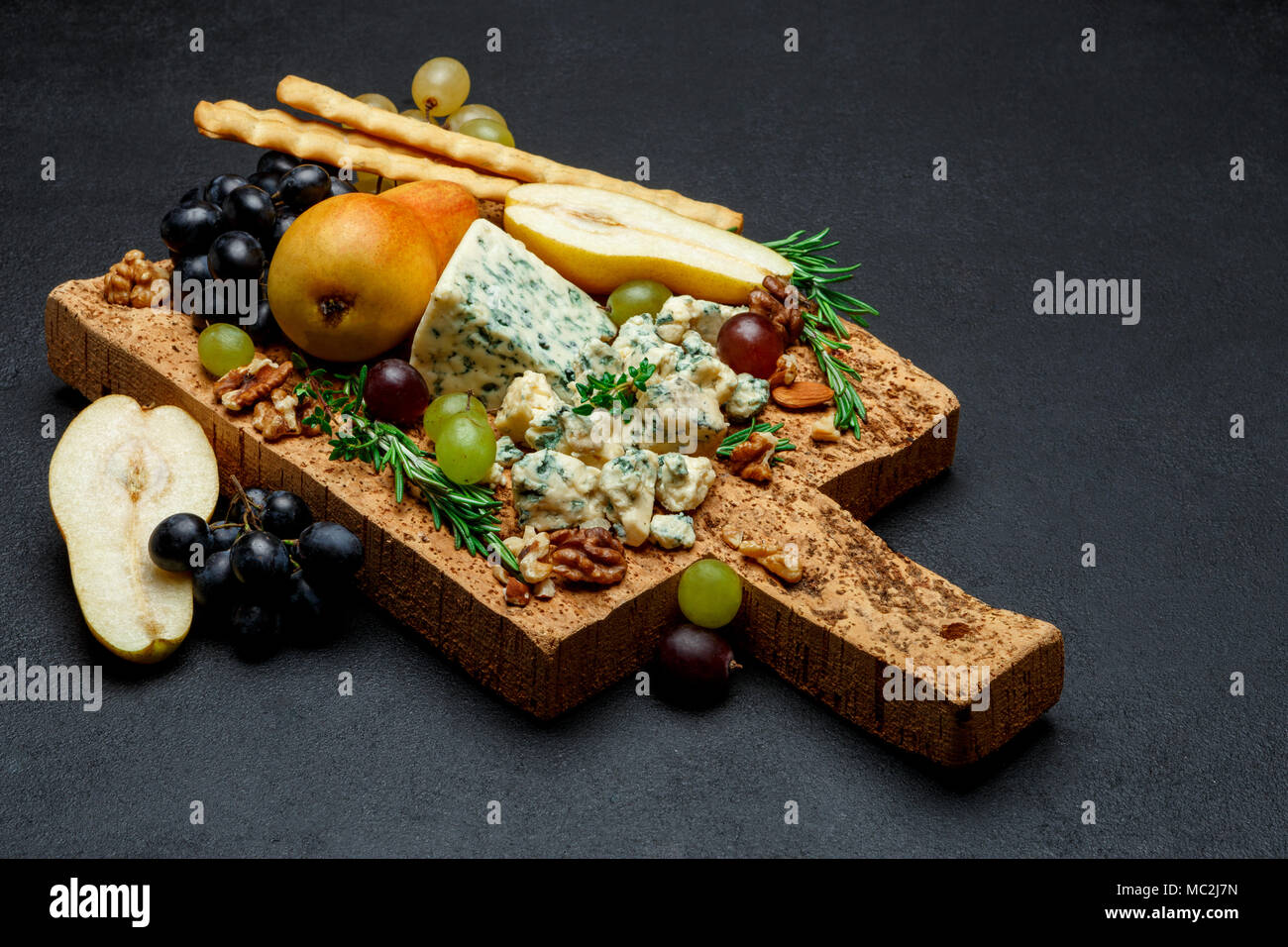 pears and cheese on wooden cutting board - Stock Image