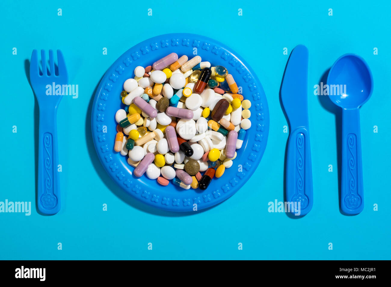 Children's plate with cutlery filled with colorful pills. Concept for overdose medicines in childrens's diet. - Stock Image