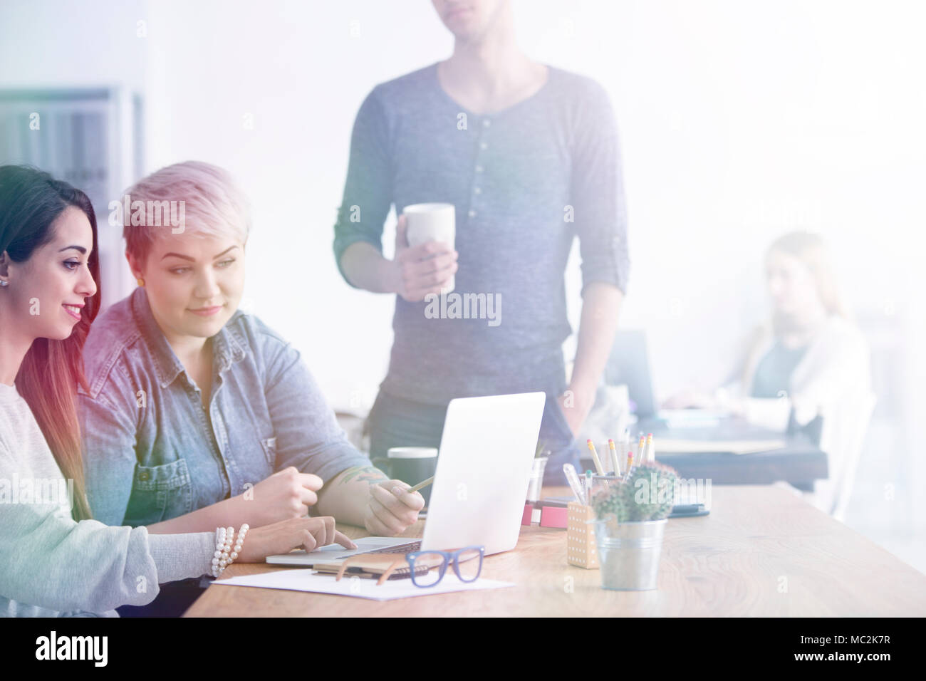 Two women sitting in an office with laptop and man standing next to them - Stock Image
