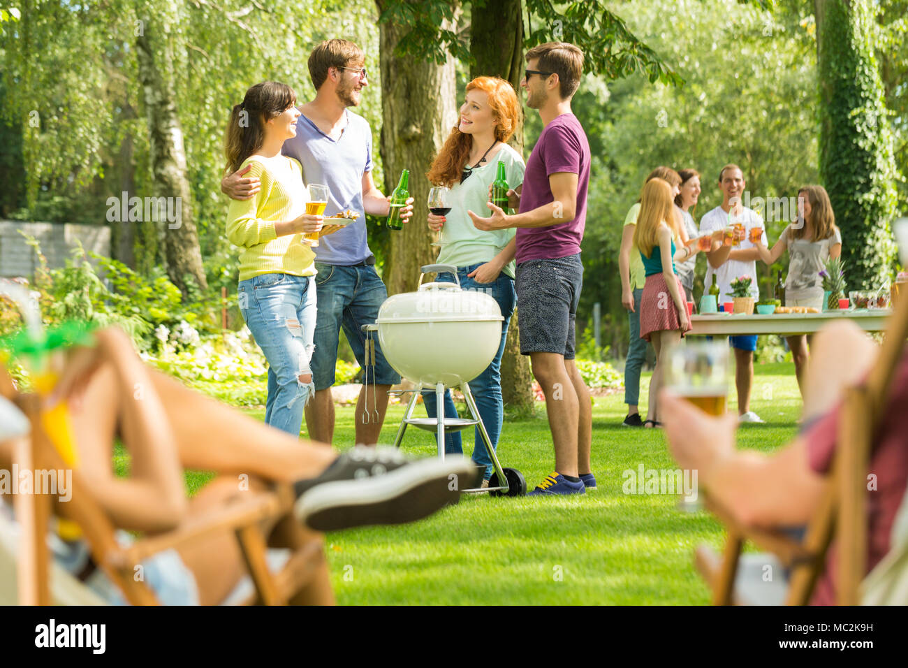 Group of young friends talking on sunny day, enjoying summer holidays drinking beer and having barbecue party in nature Stock Photo