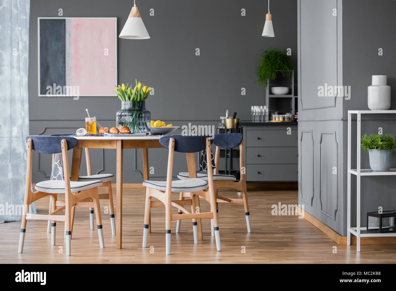 Wooden Paint Dipped Chairs Around A Small Dining Table With Pastries And An Abstract Painting On A Gray Wall Of A Dining Room Interior With Plants Stock Photo Alamy