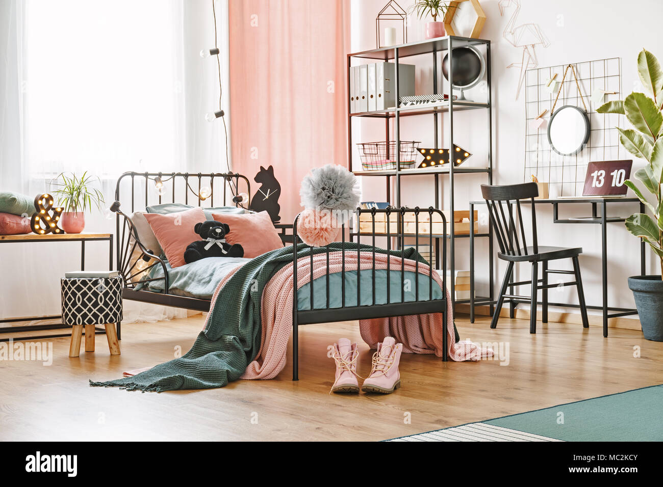 Black Teddy Bear Placed On A Metal Bed With Bedclothes And Blankets Standing In Bright Room Interior With Pink Accents Stock Photo Alamy