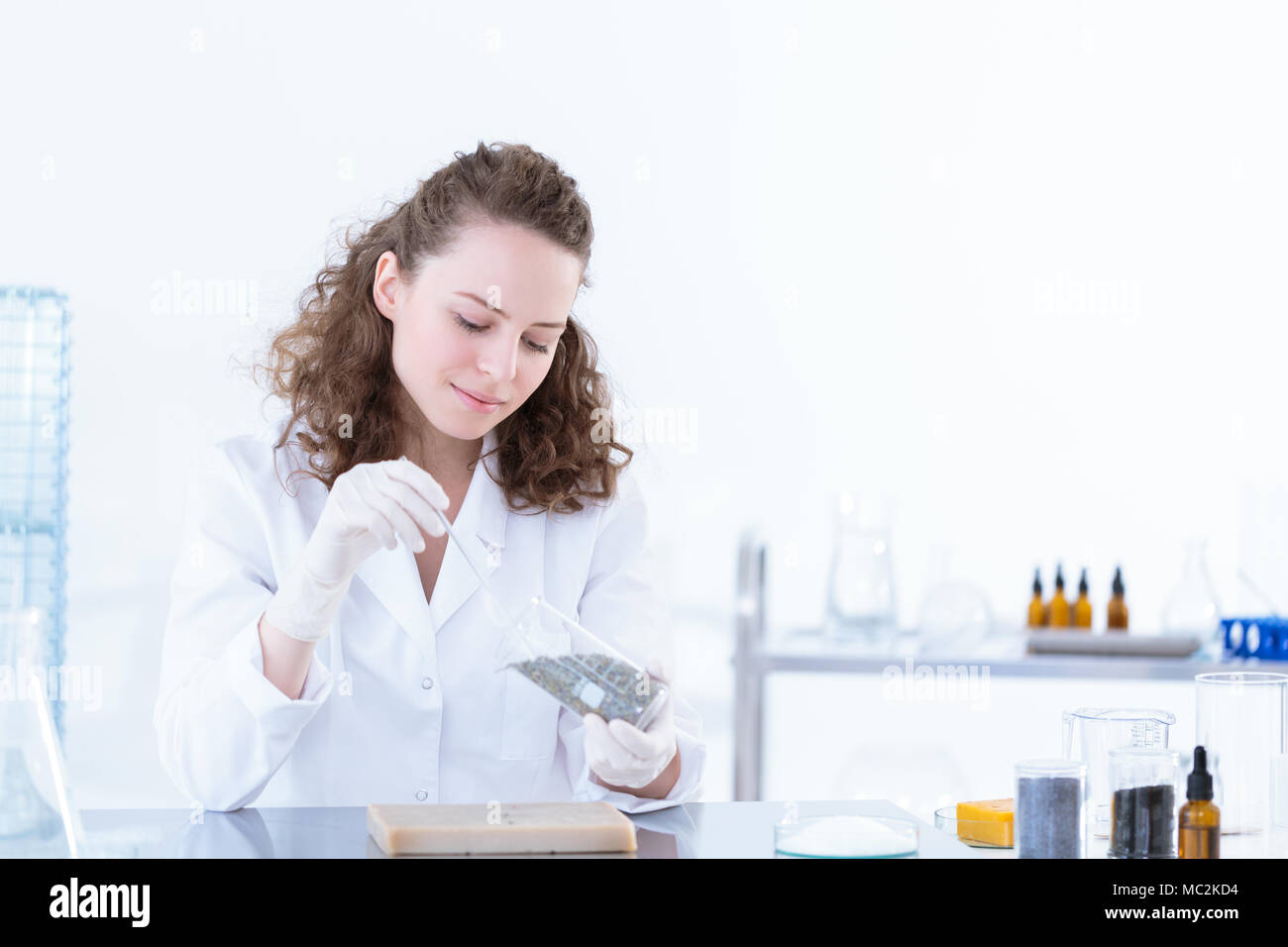 Laborer woman taking a sample of a material for tests in the laboratory - Stock Image