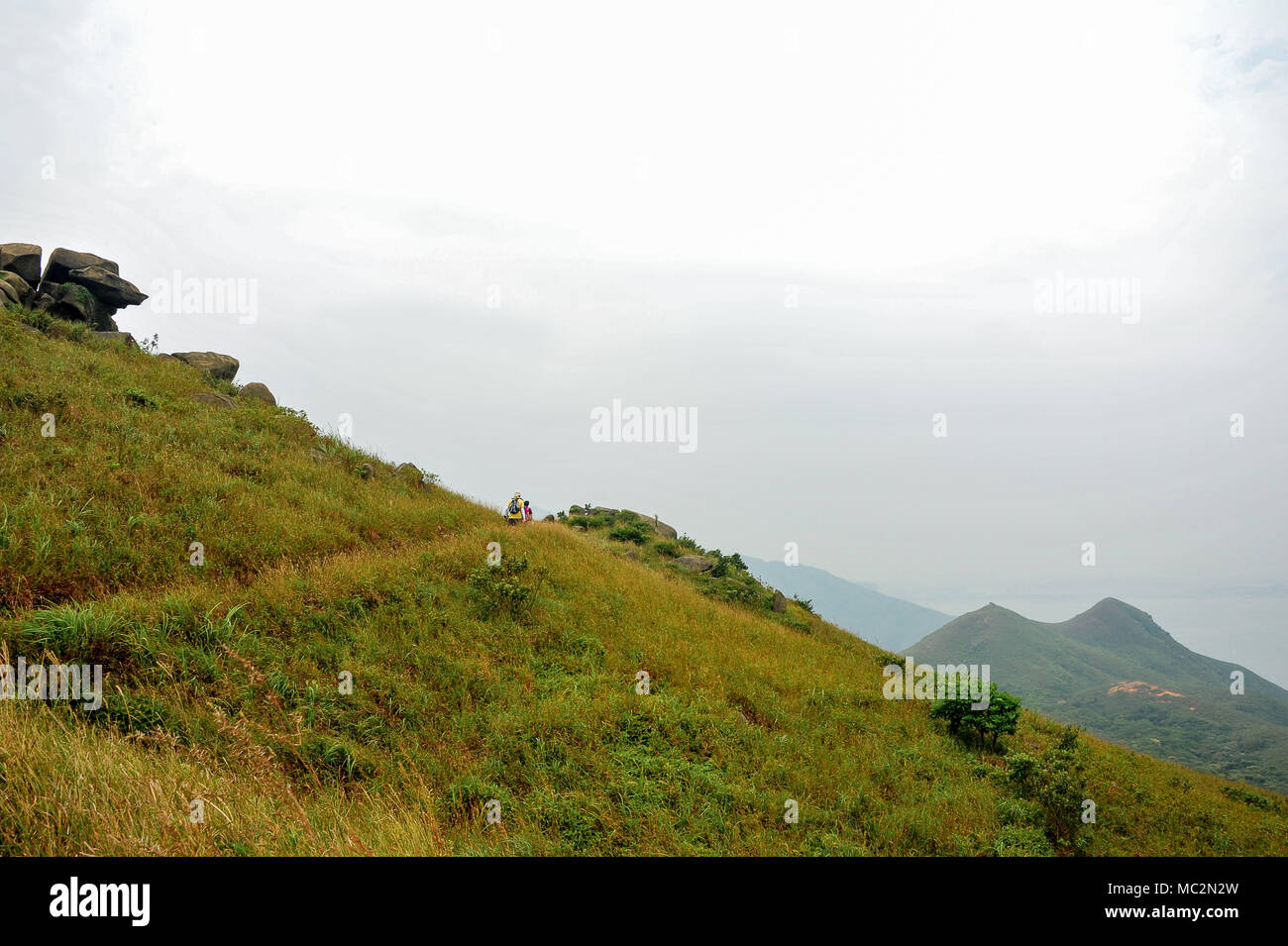 Hikers on mountain trail, Silver Mine Bay, Lantau Island, Hong Kong. Panoramic views along grassy slope to distant peaks - Stock Image