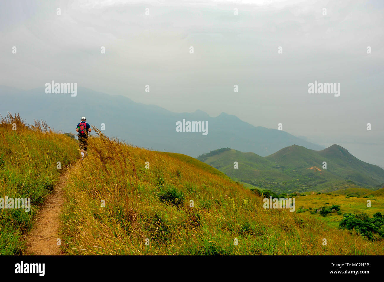 Man carrying backpack hiking on mountain trail, Silver Mine Bay, Lantau Island, Hong Kong. Panoramic views along grassy slope to distant peaks. - Stock Image