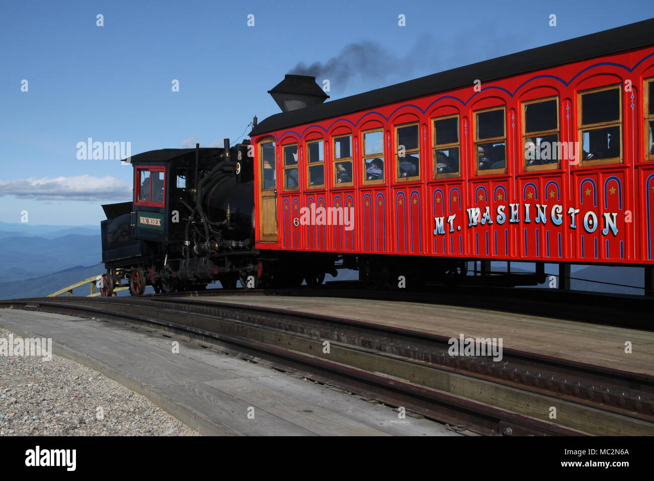 Rack and pinion locomotive pushing coach up the mountain on the Mt. Washington Cog Railway in New Hampshire - Stock Image