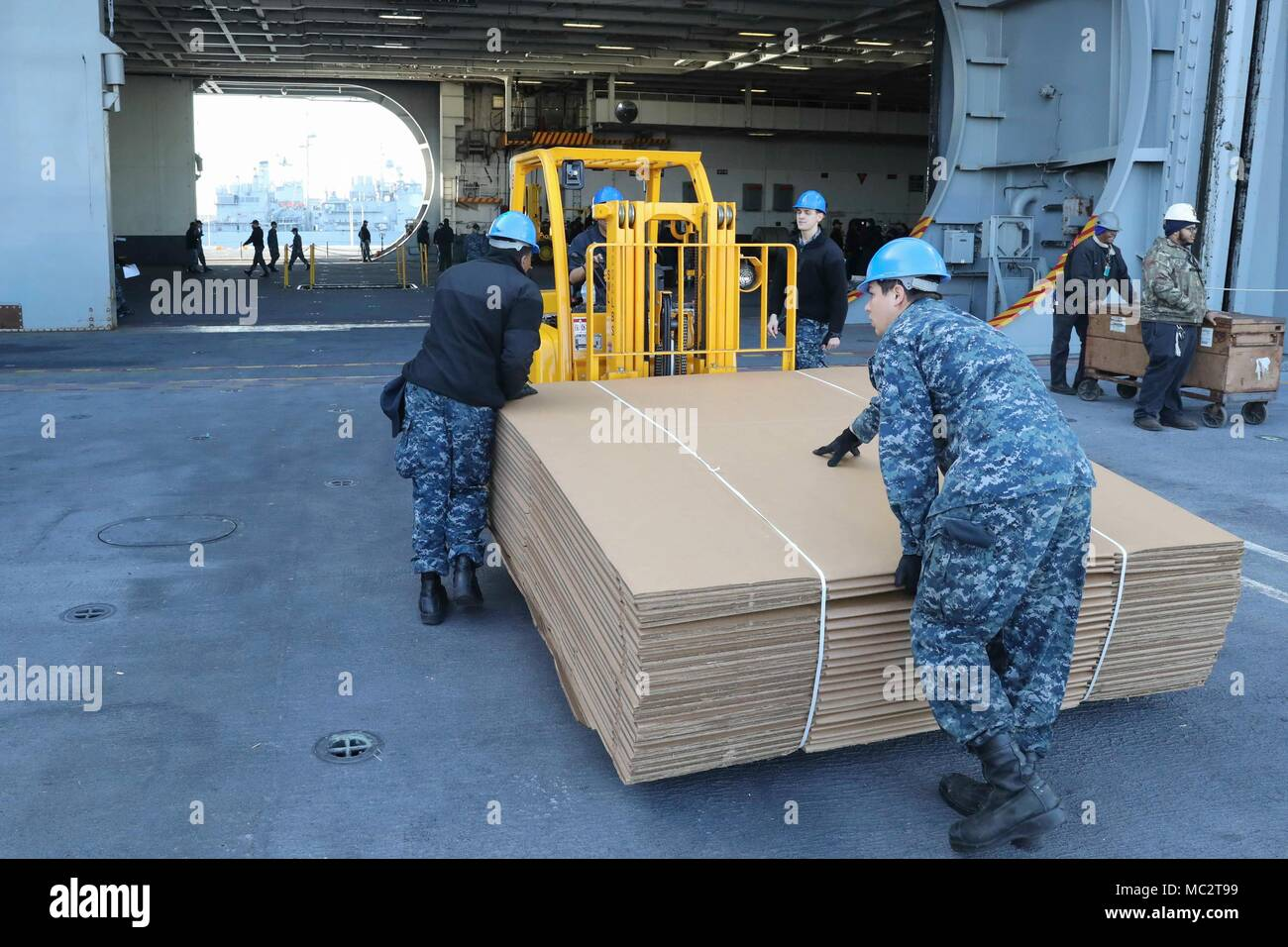 180124-N-PW716-0018 NORFOLK (Jan. 24, 2018) Sailors assigned to the Nimitz-class aircraft carrier USS Abraham Lincoln (CVN 72) move supplies into the hangar bay. (U.S. Navy photo by Mass Communication Specialist 3rd Class Clint Davis/Released) - Stock Image