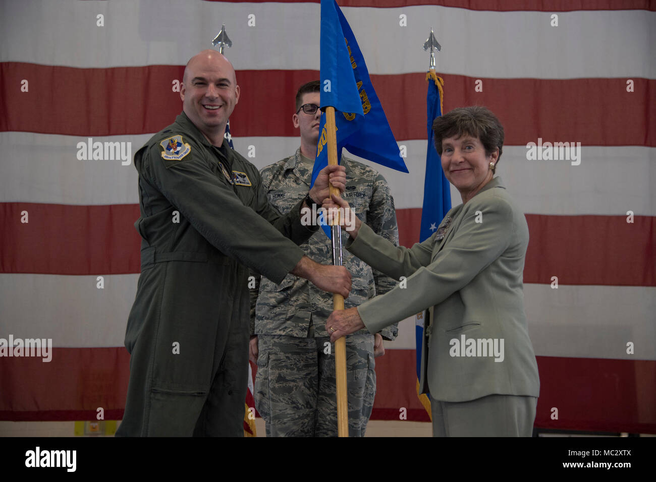 Cindy Pullen, incoming 476th Fighter Group honorary commander, accepts the guidon during an Honorary Commander Change of Command ceremony at Moody Air Force Base, Ga., Jan. 26, 2018. The Honorary Commander Program allows local community leaders to gain awareness of Moody's mission through official and social functions. (U.S. Air Force Photo by Staff Sgt. Olivia Dominique) - Stock Image