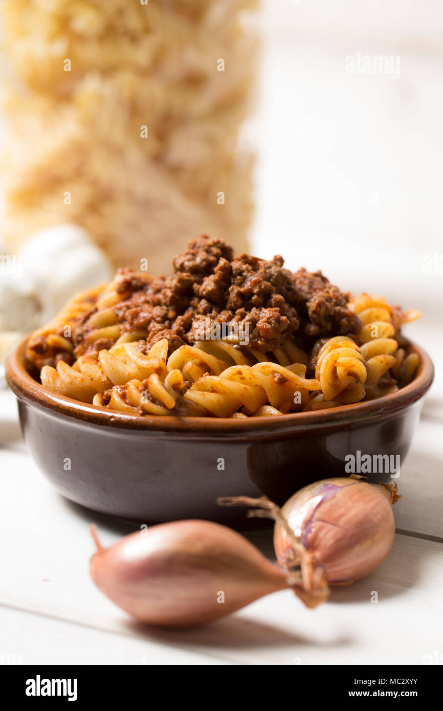 vertical closeup of traditional italian pasta with bolognese sauce with all ingredients as shallot, chese and meat  next to it, pasta is served in a t - Stock Image