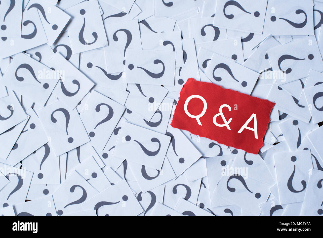 question mark on white paper and Q&A on red paper. questions and answer concept - Stock Image