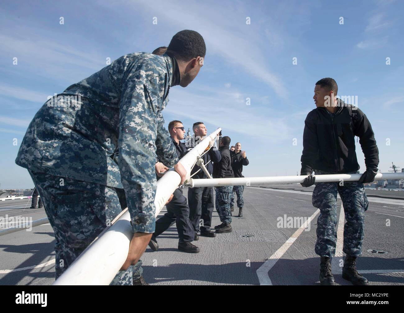 180126-N-YP246-0094 NORFOLK (Jan 26, 2018) Sailors dismantle the jack staff aboard the Nimitz-class aircraft carrier USS Abraham Lincoln (CVN 72). (U.S. Navy photo by Mass Communication Specialist Seaman Darcy McAtee/Released) - Stock Image