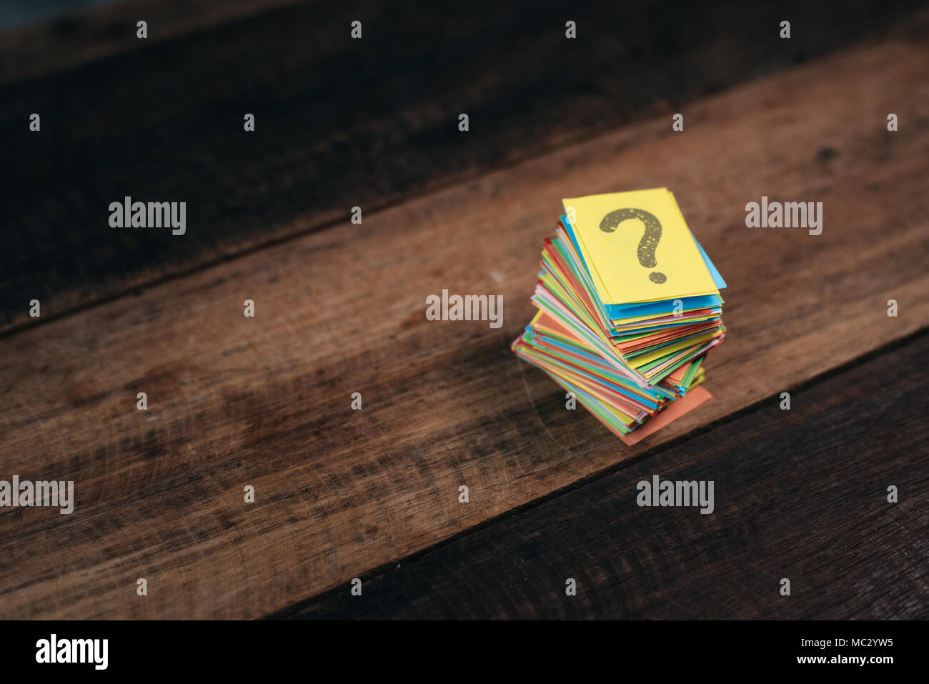 multicolored paper with QUESTION MARK on a wooden table background. questions,mystery and diversity concept. FAQ and Q&A background concept - Stock Image