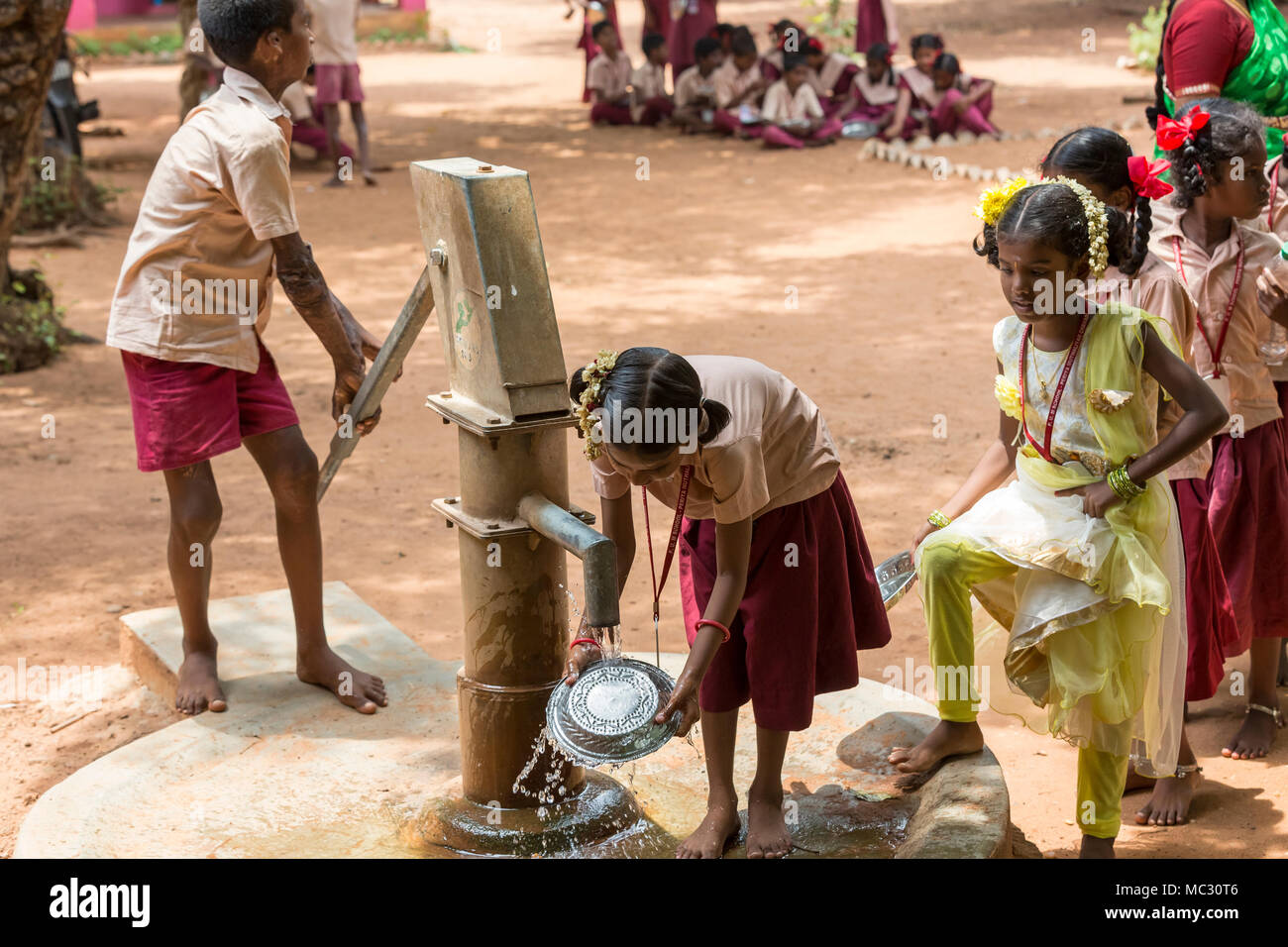 PONDICHERY, PUDUCHERY, INDIA - SEPTEMBER 04, 2017. Unidentified boys girls children clean their plates before lunch at the outdoor canteen. Stock Photo