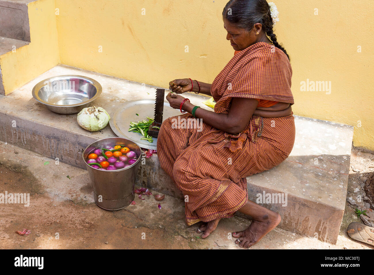 PONDICHERY, PUDUCHERY, INDIA - SEPTEMBER 04, 2017. An unidentified Indian woman cooker in the street, cutting vegetables for lunch. Stock Photo