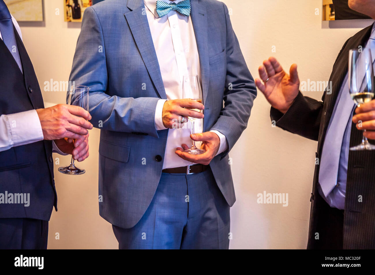 Men enjoying the party with a glass in the hand. - Stock Image