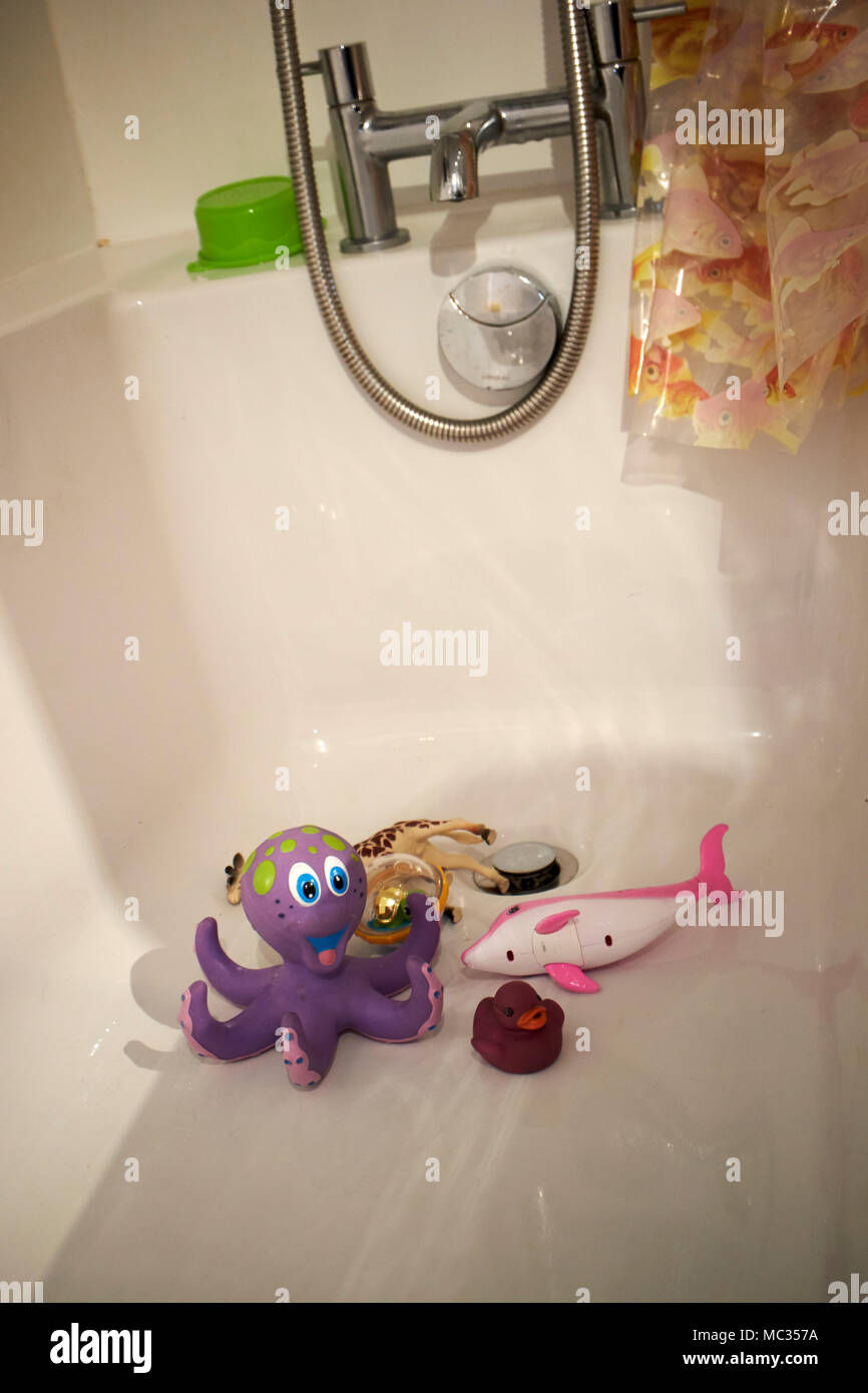 childs toys lying in an empty bath - Stock Image